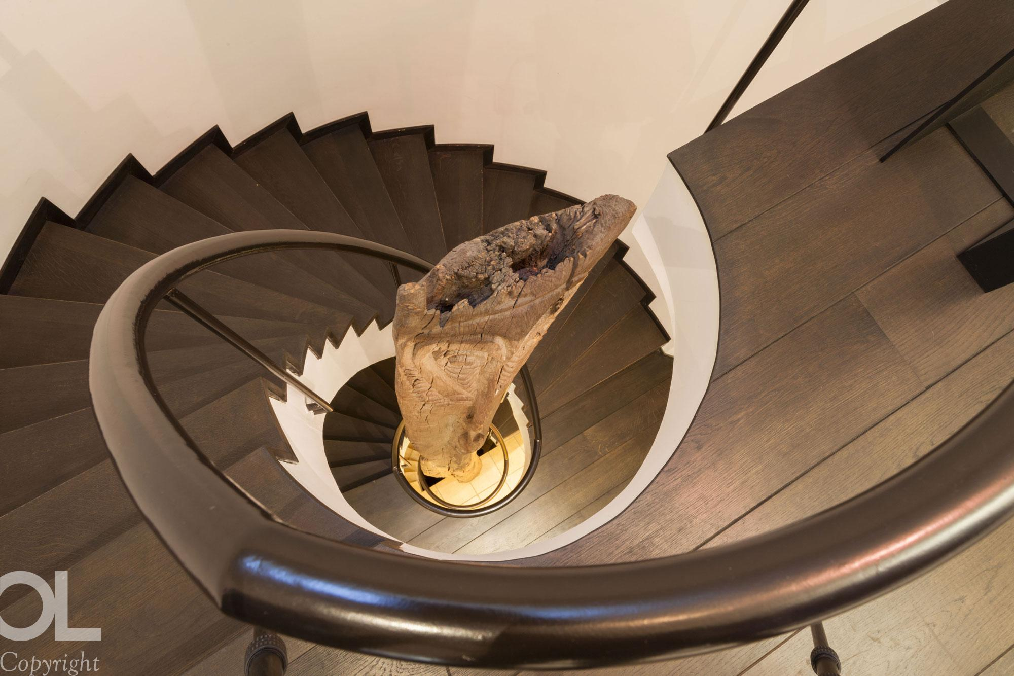 Dark wood staircase with reclaimed wood sculpture